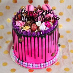 Four layers of alternating milk chocolate and vanilla cake, covered and filled with hot pink Nutella buttercream, milk chocolate drop, luster dusted strawberries, pink and purple meringues and macaroons, popcorn, Oreos, maltesers and the most beautiful hot pink edible flowers