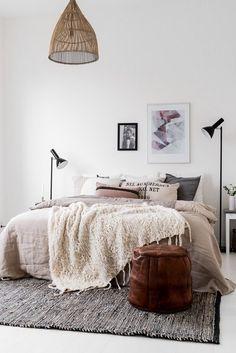 Une chambre avec du linge de lit aux tons neutres et naturels, des affiches comme tête de lit