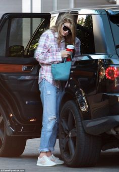 Morning after: Gigi looked a bit tired on Tuesday morning as she grabbed a large coffee...