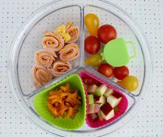Tomatoes, Turkey Rolls & Stars bento box lunch  Turkey and cheese roll-ups, tomatoes with a container of dressing for dipping, cubed apples and cheesy star crackers. Packed in round Lock & Lock container