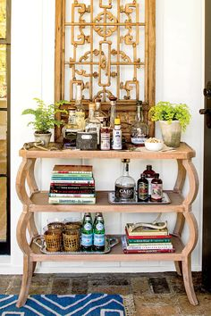 For smaller spaces that cannot comfortably contain a bar cart, a three-shelf console is a perfect replacement. Fill the shelves with books and bourbon for a handsome cart stand-in.