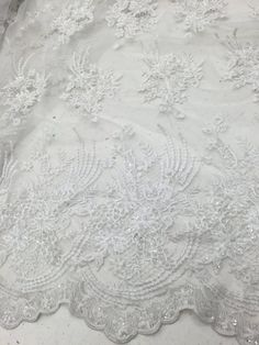 White bridal beaded lace on mesh fabric sold by by la20fabrics