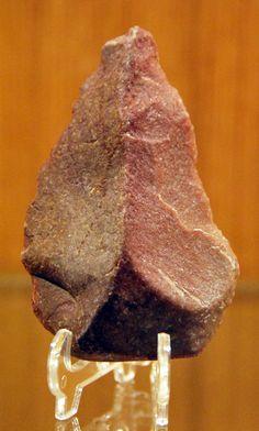 Paleolítico inferior Bifaz rojo. ~ Importancia de las rocas para el hombre, en este caso para la fabricación de armas de caza.