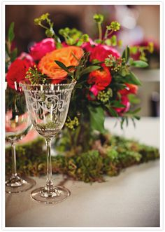 Bright pink and orange flower centerpiece with moss on the bottom.