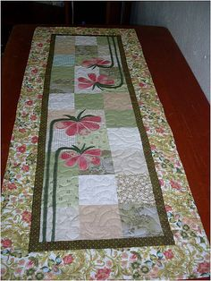 Table runner with pink appliqued flowers.