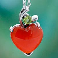 With a sigh of romance India's Shanker designs this necklace. A heart glows bright when cut from red hot heat-treated onyx. Cooled by peridot, the gems are set in sterling silver for a pendant necklace that is crafted by hand. .925 Sterling silver