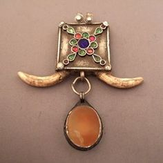"""Silver, carnelian Turkmenistan and glass paste, teeth, Afghanistan Description : A beautiful pendant that blends an old silver and carnelian small pendant from Turkmenistan, glass paste and silver items typical of nomadic art craftsmen of Aghanistan (Cushi) ... In the center of the box which is 1,29inch x 1,73 inch, pretty floral arabesques in glass paste ... Weight:45,15gr Height:3,5 inch For sale : on my website www.halter-ethnic.com...see """"Necklaces and pendants"""""""