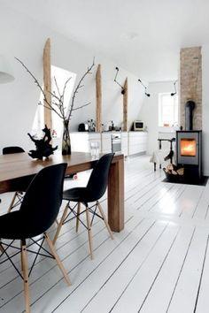 Eetkamer met witte houten vloer en houtkachel.