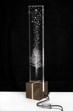 Description A wooden cube sustains a pmma stele, which is engraved with a representation of a leafless tree in a non-season. Table Lamp Wood, Wooden Lamp, Wooden Diy, Table Lamps, Light Art, Lamp Light, Plexiglas Led, Gravure Laser, Wooden Cubes