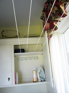 Hidden retractable indoor clothesline - another space-saving solution to indoor clothes drying.  This blogger used a purchased retractable line but integrated it into a cupboard.