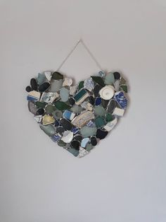 A heart shaped wall hanging made from treasure washed up and collected on the beach. Sea worn fragments of pottery, green, seafoam and white sea glass. Dotted with St Bees grey sea polished pebbles. Simply collected, washed and placed together telling the history and beauty of our