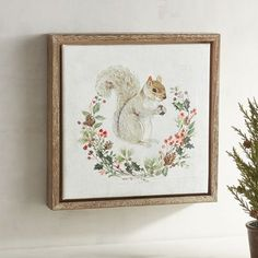 Deck your walls with this sweet seasonal squirrel wearing her little red mittens and bordered by a pine frame. She's wreathed by holiday greenery and will bring winter charm to any room.