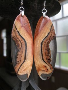 Afzelia is a very beautiful exotic wood that grows in South East Asia. This one specific came from Viet Nam. I know for a fact this tree died of natural causes due to all the worm holes in this burl...    The earring pendants measure three inches long by one inch wide...