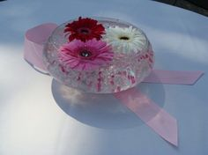 Breast Cancer Fundraiser Centerpiece.  This unique centerpiece features a round glass bowl filled with floral beads. These help hold three daisies at the top of the centerpiece. The centerpiece sits atop a pink ribbon folded in the famous shape.