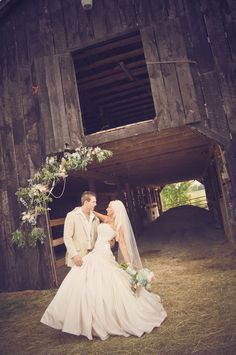 bride and groom in front of a barn