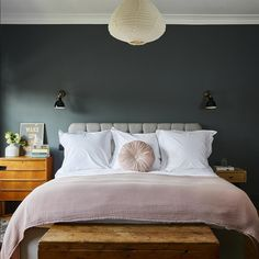 Dark walls in a bedroom are not to everyone's taste, but keep the look light and airy by introducing furniture in natural wood, like the bedside table from Maisons du Monde. A plush grey headboard and blush bedding accents compliment the dark moody walls to create a soft and stylish master bedroom.