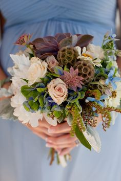 Interesting combination of antique hydrangea, touches of blue, blush peonies, roses and lavender succulents.