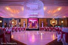 This colorful Indian wedding reception features beautiful lighting.
