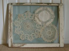 Antique window frame used to display old lace doilies. Just staple some inexpensive screen to the back of the frame and stitch on your bits to display!