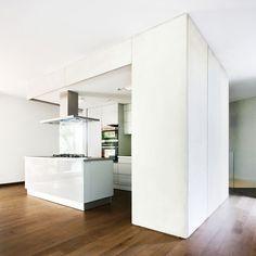 cocina abierta con isla central para zona de cocción, módulo para electrodomésticos y armarios de almacenaje como separación, suelo parquet