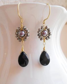 Subtle and sophisticated, Maurice gemstone beaded earrings are an interesting option for everyday. Luminous gray shell pearls are wire wrapped with gold filled wire and surrounded by gold pyrite faceted rondelles. At their bottom dangles a lovely black onyx faceted almond briolette