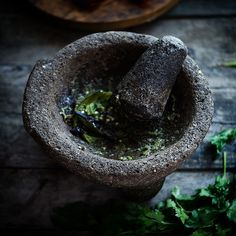 Green sauce of serrano pepper in stone mortar.