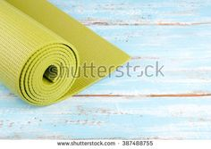 Yoga mat on a wooden background. Equipment for yoga. Concept  healthy lifestyle and sport. Lots of copy space. Selective focus