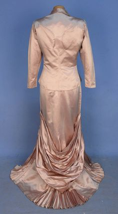 ADRIAN STRAPLESS EVENING GOWN and JACKET, 1940's. Dusty pink silk having asymmetrical semi boned bodice with diagonal drape ruched into side seam, trained skirt with three pleated gores and lower back swag. Matching jacket with long sleeve pleated at lightly padded shoulder, self buttons at waist and pieced seam detail on back.