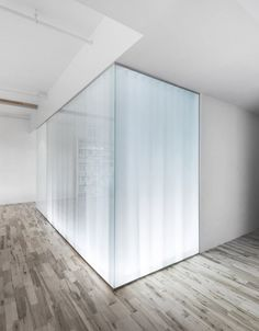 Light and translucent curtains behind a glass wall adding light to a dark interior space. Espace St.-Dominique by Anne Sophie Goneau.