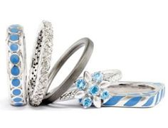 This set of five sterling silver rings includes two blue enameled bands one of which is square in shape, a black ruthenium-plated satin finished band, a diamond eternity band prong set with I3 clarity H-I white stones and a sparkling flower ring prong set with blue topaz stones. Click on ....