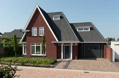 Bijzondere kapvormen voorzien van keramische dakpannen, samen rode handvorm gevelsteen