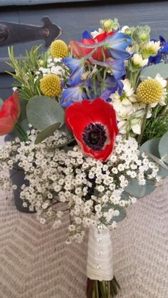 Pretty field style bouquet of anemones, delphinium, gypsophila and stocks with ivory cotton tibbon finish
