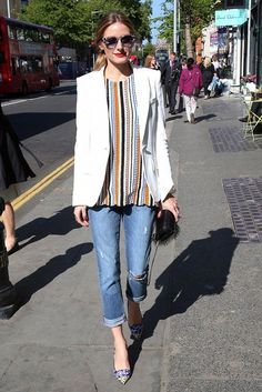 Olivia Palermo steps out in a multi-color striped top, white blazer, blue cuffed jeans and pointed toe heels.