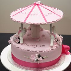 This carousel cake is covered with fondant, perfect for your baby girl's 1st birthday.