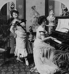 Two alluringly attired Edwardian ladies put on a song-and-piano show in 1903, possibly brothel?