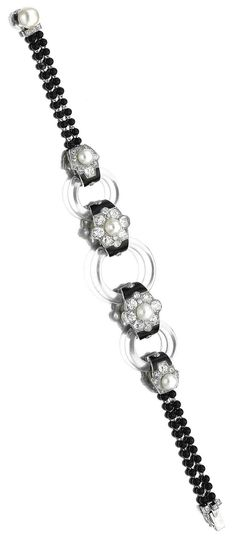 Cartier - An Art Deco rock crystal, onyx, enamel, seed pearl and diamond bracelet, circa 1925. Set to the centre with three rock crystal annular links, spaced by seed pearls and circular-cut diamond clusters flanked by black enamel, continuing to two rows of onyx beads, signed Cartier and numbered, French assay and indistinct maker's marks. #Cartier #ArtDeco #bracelet