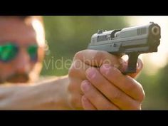 Young Man Is Shooting From a Gun (Stock Footage)