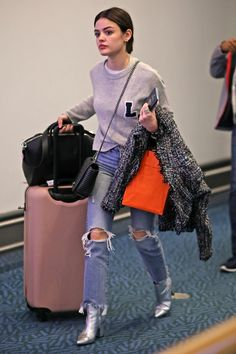 Lucy Hale wearing Chanel Coco Boy Flap in Black and Herschel Supply Co. Trade Suitcase in Ash Rose