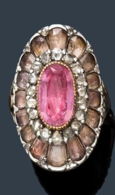 IMPERIAL TOPAZ AND DIAMOND RING, ca. 1830. Silver over yellow gold. Decorative ring centring one oval pink topaz, framed by 18 rose-cut diamonds, within a border of 16 cut glass stones. #antique #ring