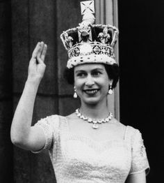 Queen Elizabeth II, wearing the Imperial Crown, smiles and waves to crowd from balcony of Buckingham Palace on June 2, 1953 in London, on returning from Westminster Abbey following her coronation