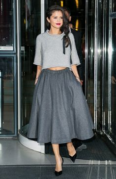 Selena Gomez wears a cropped sweater, full wool gray skirt, and pointed-toe pumps