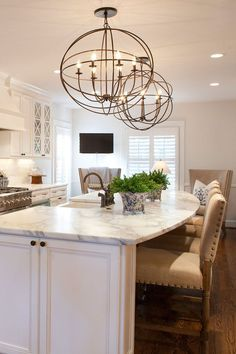 Stunning kitchen with white cabinets, farmhouse sink, large island with seating and granite countertops.