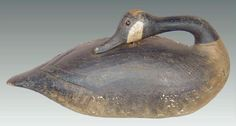 """Decoys Unlimited Summer Auction 7/26-27/2015 lot 275. A superb large sculpture of a preening Canada Goose c. 1900 from the North Shore of Massachusetts, branded 'PACKARD"""" twice on the underside. A full-bodied, stick-up decoy with a turned-back head and a long graceful neck. The decoy has incised bill detail, glass eyes, hand-carved knife and rasp marks, and raised primary and secondary wing tips. The head and neck are secured to the body with large nails and there is a deep 3/4 inch wide…"""