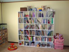 """The wall bookcase is made from four, 9-unit Closetmaid Cubeicals units, available from Lowes or Target. The top two rows are """"my"""" stuff such as homeschool support books, curriculum, history/culture books, etc. I used my label maker to label the necessary cubes. The cubes across the bottom hold some learning games, floor puzzles, our multicolored masking tape dispenser {DiscountSchoolSupply.com}, our snap case of scissors, glue, and paper punches, and our clear paint buckets holding crayons…"""