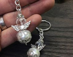 Angel keychain Beautiful Angel Keychains made with glass pearl body and a fire polished round crystal bead head. The angel is then topped with diamond halo and beautiful metal heart wings. Since the keychains have no religious icon, they can be used for any event, ranging from baby shower, Baptism, Christening or wedding. Measure 3 in total length. Available in two colors; Ivory pearl with Gold Wings, chain and halo or White pearl with Silver Wings, chain and halo.