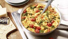 Kunterbunte Tortelloni Pfanne mit Blattspinat, frischen Cocktailtomaten und sämiger Sahne. Darüber noch würzigen Parmesan streuen.