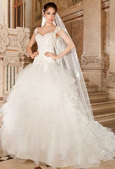 Brides: Demetrios - Sensualle. This romantic tulle gown features a sweetheart neckline dropped waist and lace-up closure. The bodice and sheer cap sleeves are embellished with embroidered lace. The multi-tiered full ruffled skirt flows into a chapel length train.