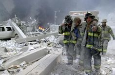 """New York City firefighters carry an injured firefighter away from the rubble of the twin towers at the World Trade Center. The New York City Fire Department suffered 343 fatalities on Sept. 11, 2001, """"the largest loss of life of any emergency response agency in history,"""" according to the 9/11 Commission Report"""