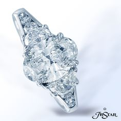 Style 2031  Stunning handcrafted ring featuring a 1.66ct oval diamond with half moon diamond sides and round diamonds. Platinum.