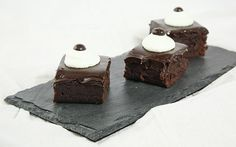 A photo of three Truffle Brownies with Espresso decorated with a mound of whipped cream and a chocolate covered espresso bean displayed in a...